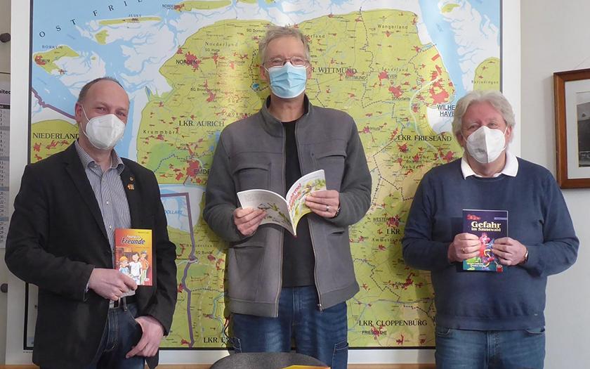Der Grundschulleiter nimmt die Bücker vom Rotary-Club entgegen