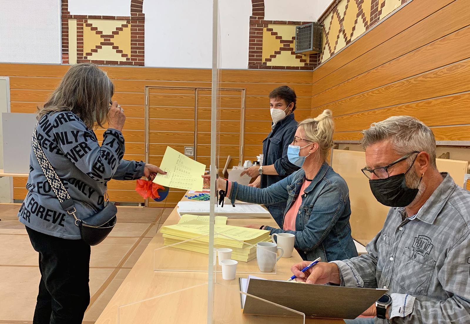 Wählerin erhält ihre Stimmzettel im Norderneyer Wahllokal